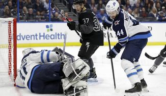 Winnipeg Jets defenseman Josh Morrissey (44) clears the puck after Tampa Bay Lightning center Yanni Gourde (37) took a shot on goaltender Connor Hellebuyck (37) during the second period of an NHL hockey game Saturday, Nov. 16, 2019, in Tampa, Fla. (AP Photo/Chris O'Meara)