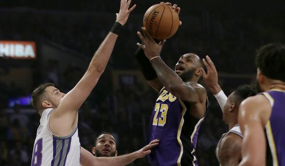 Los Angeles Lakers forward LeBron James, center, drives to the basket against Sacramento Kings forward Nemanja Bjelica, left, forward Richaun Holmes, right, and guard Cory Joseph (9) during the first half of an NBA basketball game in Los Angeles, Friday, Nov. 15, 2019. (AP Photo/Alex Gallardo)