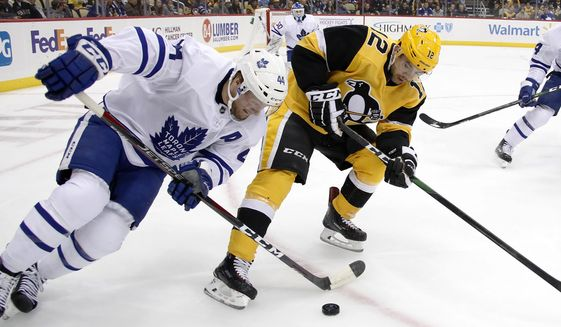 Toronto Maple Leafs' Morgan Rielly (44) battles Dominik Simon (12) for the puck during the second period of an NHL hockey game in Pittsburgh, Saturday, Nov. 16, 2019. (AP Photo/Gene J. Puskar)