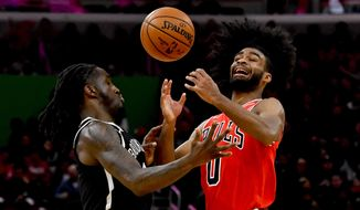 Brooklyn Nets forward Taurean Prince, left, and Chicago Bulls guard Coby White try to gather in a loose ball during the first half of an NBA basketball game Saturday, Nov. 16, 2019, in Chicago. (AP Photo/Matt Marton)