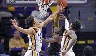 LSU forward Courtese Cooper (21) blocks the shot of Nicholls guard Andre Jones (13), center, as teammate Charles Manning Jr. (11), right, helps in the first half of an NCAA college basketball game, Saturday, Nov. 16, 2019, in Baton Rouge, La. (AP Photo/Bill Feig)