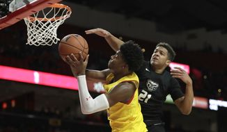 Maryland guard Hakim Hart, left, goes up for a shot as Oakland guard Madison Monroe (21) defends during the second half of an NCAA college basketball game, Saturday, Nov. 16, 2019, in College Park, Md. Maryland won 80-50. (AP Photo/Julio Cortez)