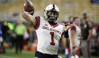 Oklahoma quarterback Jalen Hurts warms up prior to an NCAA college football game against Baylor in Waco, Texas, Saturday, Nov. 16, 2019. (AP Photo/Ray Carlin)