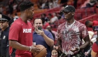 Miami Heat forward Jimmy Butler, left, talks with Manchester United midfielder Paul Pogba, right, before a NBA basketball game between the Miami Heat and New Orleans Pelicans, Saturday, Nov. 16, 2019, in Miami. (AP Photo/Lynne Sladky)