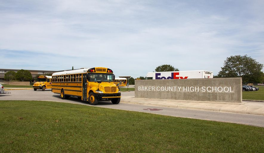 In this Oct. 17, 2019 photo, buses depart from Baker County High School in Glen St. Mary, Fla. Unease spread across Baker County when authorities arrested a 15-year-old who they say planned a massacre at the county's only high school. Anger grew when a judge dismissed second-degree felony charges against the boy.(AP Photo/Bobby Caina Calvan)