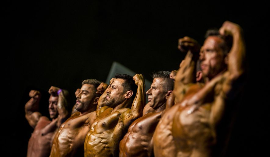 In this Saturday, Nov. 9, 2019 photo, contestants pose on stage during the 51st national body building competition held in Estepona, Spain. Spanish absolute championship is the largest yearly event on the national body-building calendar, where over 500 competitors compete for the title of Spanish champion on 40 different categories. (AP Photo/Javier Fergo)