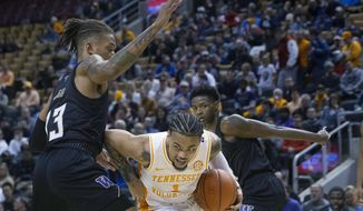 Tennessee's Lamonte Turner, center, drives past Washington's Hameir Wright during the first half of an NCAA college basketball game in the James Naismith Classic, in Toronto on Saturday, Nov. 16, 2019. (Chris Young/The Canadian Press via AP)