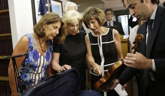FILE - In an August 6, 2015 file photo, FBI agent Chris McKeogh, right, shows sisters Amy Totenberg, left, Nina Totenberg, second from left, and Jill Totenberg the Ames Stradivarius violin that was stolen from their father 35 year ago, in New York. The Stradivarius violin stolen four decades ago from the late virtuoso Roman Totenberg and returned to his family by a federal prosecutor came alive again _ at the crime scene, playing the same music. At a concert in Cambridge, Massachusetts, 19-year-old star violinist Nathan Meltzer revived the priceless instrument of the Polish-born musician on Friday evening, Nov. 15, 2019.   (AP Photo/Seth Wenig, File)