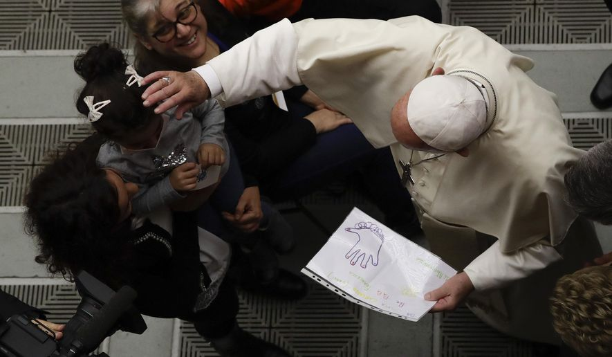 Pope Francis holds a drawing by a child in the Paul VI Hall during an audience with Baby Jesus children hospital, Saturday, Nov. 1, 2019. (AP Photo/Alessandra Tarantino)