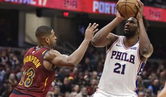 Philadelphia 76ers' Joel Embiid (21) shoots over Cleveland Cavaliers' Tristan Thompson (13) in the first half of an NBA basketball game, Sunday, Nov. 17, 2019, in Cleveland. (AP Photo/Tony Dejak)