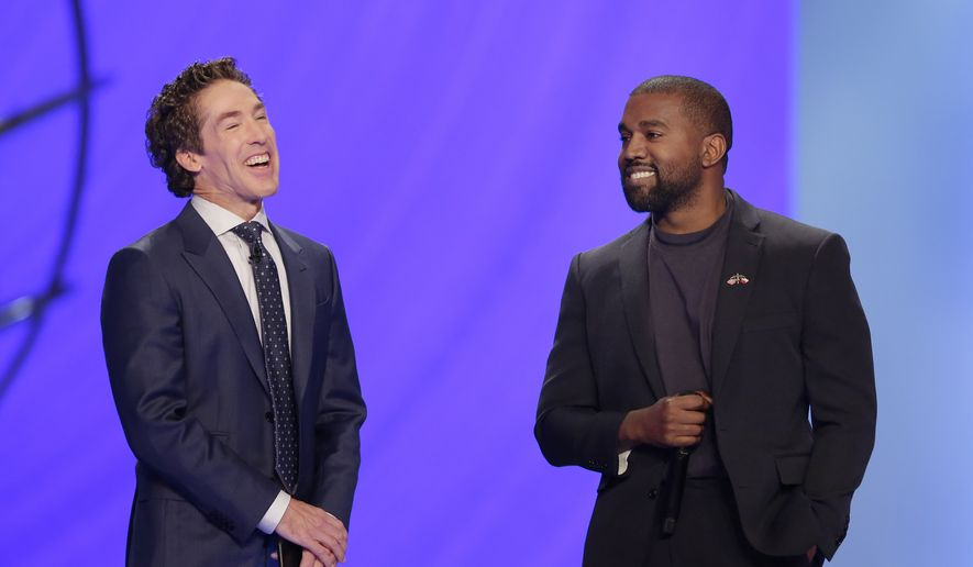 Kanye West, right, answers questions from senior pastor Joel Osteen, left, during a service at Lakewood Church, Sunday, Nov. 17, 2019, in Houston. (AP Photo/Michael Wyke)