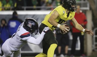 Arizona's Tony Fields II, left, sacks Oregon quarterback Justin Herbert during the second quarter of an NCAA college football game Saturday, Nov. 16, 2019, in Eugene, Ore. (AP Photo/Chris Pietsch)