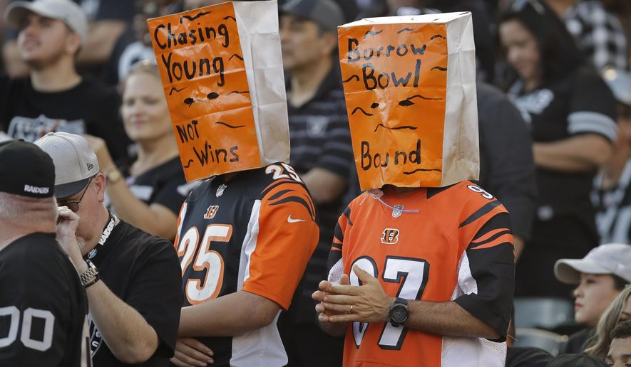 Cincinnati Bengals fans wears paper bags on their heads during the second half of an NFL football game against the Oakland Raiders in Oakland, Calif., Sunday, Nov. 17, 2019. (AP Photo/Ben Margot)
