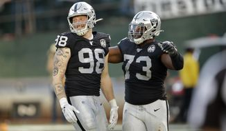 Oakland Raiders defensive end Maxx Crosby (98) is greeted by defensive tackle Maurice Hurst (73) after sacking Cincinnati Bengals quarterback Ryan Finley during the second half of an NFL football game in Oakland, Calif., Sunday, Nov. 17, 2019. (AP Photo/Ben Margot)
