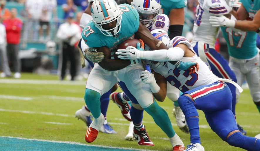 Miami Dolphins running back Kalen Ballage (27) runs for a touchdown, as Buffalo Bills strong safety Micah Hyde (23) attempts to tackle, during the first half at an NFL football game, Sunday, Nov. 17, 2019, in Miami Gardens, Fla. (AP Photo/Wilfredo Lee)