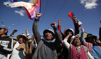Supporters of former President Evo Morales stand next to a burning tire at a blockade along a road leading to the state-own Senkata gas filing plant in El Alto, Bolivia, Sunday, Nov. 17, 2019. Bolivia's political crisis turned deadly after security forces opened fire on supporters of Morales in Sacaba on Nov. 15, killing multiple people and injuring dozens. (AP Photo/Natacha Pisarenko)