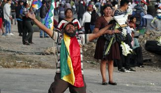 """A coca leaf producer kneels holding a bible with his arms outspread asking police to open the way so a march by backers of former President Evo Morales may continue to Cochabamba, Bolivia, Saturday, Nov. 16, 2019. Officials now say at least eight people died when Bolivian security forces fired on Morales supporters the day before, in Sacaba. The U.N. human rights chief says she's worried that Bolivia could """"spin out of control"""" as the interim government tries to restore stability following the resignation of the former president in an election dispute. (AP Photo/Juan Karita)"""