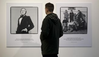 FILE - In this file photo dated Thursday Jan. 31, 2013, a man views photographs of footballers by Terry O'Neill are seen on display at the Strike A Pose: 50 Years of Football & Fashion, exhibition preview at the National Football Museum in Manchester, England.  Terry O'Neill photos seen are World Cup England soccer team captain Bobby Moore at left taken in 1975, and a gathering of some England soccer player greats taken in 1972.  Iconic photographer Terry O'Neill, who chronicled the swinging 60s generation, died Saturday Nov. 17, 2019, aged 81, according to an announcement from his licensing agency. (AP Photo/Jon Super, FILE)