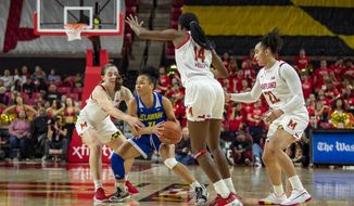 Delaware guard Paris McBride (4) tries to break away from Maryland guards Blair Watson (22), Diamond Miller (14) and Taylor Mikesell (11) during the first half of an NCAA college basketball game, Sunday, Nov. 17, 2019, in College Park, Md. (AP Photo/Brien Aho)