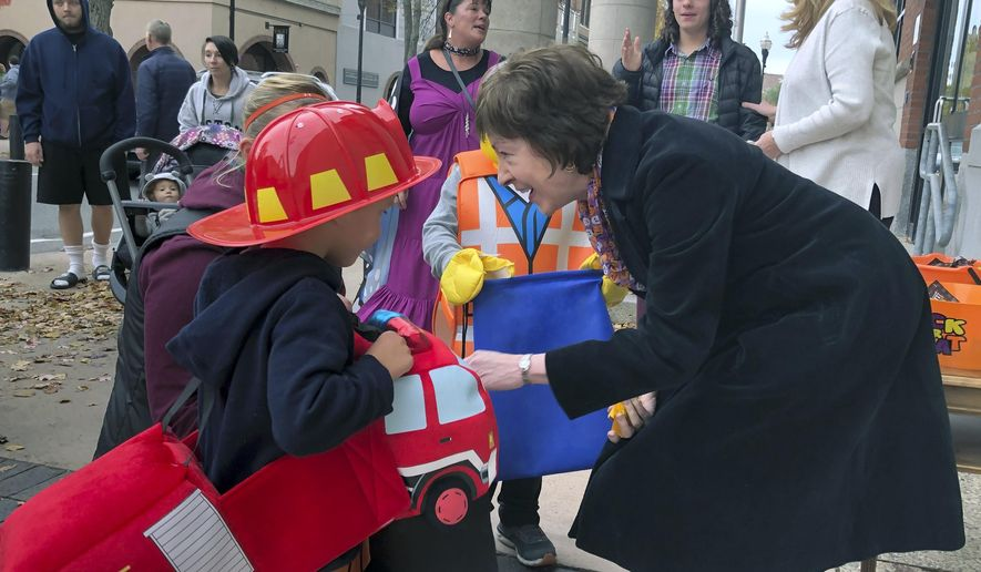 In this Friday, Oct. 25, 2019 photo, Sen. Susan Collins, R-Maine, hands out candy to children outside her office during a trick-or-treat event hosted by the local chamber of commerce in Lewiston, Maine. Collins is expected to make a formal announcement on her reelection plans later this fall. (AP Photo/David Sharp)