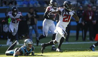 Atlanta Falcons cornerback Desmond Trufant (21) runs while Carolina Panthers running back Christian McCaffrey (22) misses the tackle during the first half of an NFL football game in Charlotte, N.C., Sunday, Nov. 17, 2019. (AP Photo/Brian Blanco)