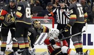 Vegas Golden Knights goalie Marc-Andre Fleury puts his glove on the head of Calgary Flames left wing Matthew Tkachuk during the second period of an NHL hockey game Sunday, Nov. 17, 2019, in Las Vegas. (AP Photo/Isaac Brekken)