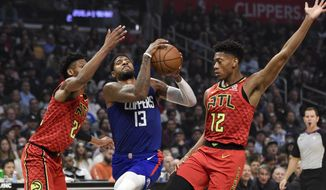 Los Angeles Clippers forward Paul George, center, drives to the basket between Atlanta Hawks forward De'Andre Hunter, right, and forward Cam Reddish during the first half of an NBA basketball game in Los Angeles, Saturday, Nov. 16, 2019. (AP Photo/Kelvin Kuo)