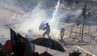 A protestor reacts as police fire tear gas at Hong Kong Polytechnic University in Hong Kong, Sunday, Nov. 17, 2019. Police fired tear gas at protesters holding out at Hong Kong Polytechnic University as overnight clashes resumed Sunday, and opposition lawmakers criticized the Chinese military for joining a cleanup to remove debris from streets. (AP Photo/Kin Cheung)