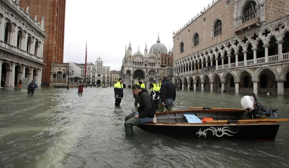 A man sits on a small boat in a flooded St. Mark square in Venice, Italy, Sunday, Nov. 17, 2019. Venetians are bracing for the prospect of another exceptional tide in a season that is setting new records. Officials are forecasting a 1.6 meter (5 feet, 2 inches) surge of water Sunday through the lagoon city. (AP Photo/Luca Bruno)