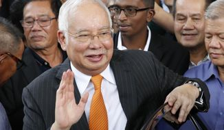 FILE - In this Nov. 11, 2019, file photo, former Malaysian Prime Minister Najib Razak waves as he leaves Kuala Lumpur High Court in Kuala Lumpur, Malaysia. Najib's third corruption trial has started Monday, Nov 18, 2019, with prosecutors saying he tampered with a government audit on the 1MDB state investment fund in a bid to avoid civil and criminal proceedings. (AP Photo/Vincent Thian, File)