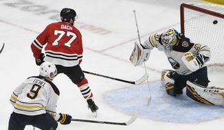 Chicago Blackhawks center Kirby Dach (77) scores a goal on Buffalo Sabres goaltender Carter Hutton (40) during the second period of an NHL hockey game Sunday, Nov. 17, 2019, in Chicago. (AP Photo/David Banks)