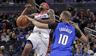 Orlando Magic's Evan Fournier (10) knocks the ball away from Washington Wizards' Bradley Beal as he goes up for a shot during the first half of an NBA basketball game, Sunday, Nov. 17, 2019, in Orlando, Fla. (AP Photo/John Raoux) ** FILE **