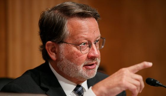 Sen. Gary Peters, Michigan Democrat, is accused of exploiting a legal gray area to improperly coordinate with VoteVets, a progressive veterans advocacy group. His campaign website and an ad the group bought used the same photos and videos. (Associated Press)
