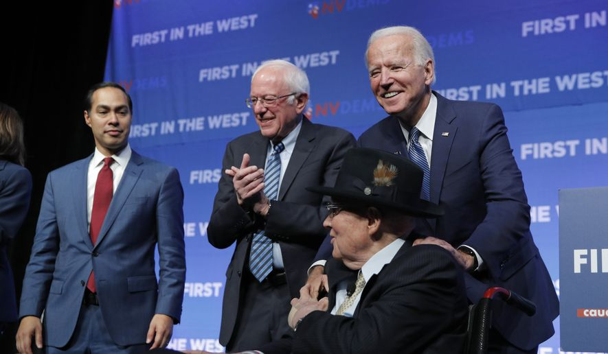 Former Vice President and Democratic presidential candidate Joe Biden, right, shakes hands with former U.S. Sen. Harry Reid beside Democratic presidential candidates, former Housing and Urban Development Secretary Julian Castro, left, and Sen. Bernie Sanders, I-Vt., during a fundraiser for the Nevada Democratic Party, Sunday, Nov. 17, 2019, in Las Vegas. (AP Photo/John Locher)