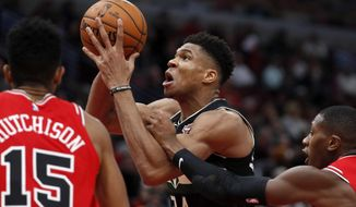 Milwaukee Bucks' Giannis Antetokounmpo, center, drives to the basket past Chicago Bulls' Chandler Hutchison (15) and Kris Dunn during the second half of an NBA basketball game Monday, Nov. 18, 2019, in Chicago. (AP Photo/Charles Rex Arbogast)