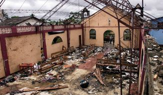 FILE - This May 8, 2002 file photo shows a destroyed church in Bojaya, in Colombia's northwestern state of Choco. The church was destroyed on May 2, 2002, when rebels of the Revolutionary Armed Forces of Colombia, FARC, fired homemade missiles during fighting with paramilitaries killing more than a hundred civilians, mostly women and children. Family members of the victims held a ceremony Monday, Nov. 18, 2019, in Bojaya following a painstaking process in which scientists used DNA to identify the remains of 79 people initially buried in a mass grave. (AP Photo/Ricardo Mazalan, File)
