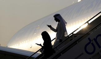 People climb down the stairs of a plane, on the opening day of Dubai Airshow, in the United Arab Emirates, Sunday, Nov. 17, 2019. The biennial airshow has opened as major Gulf airlines reign back big-ticket purchases after a staggering $140 billion in new orders were announced at the 2013 show before global oil prices collapsed. (AP Photo/Kamran Jebreili)