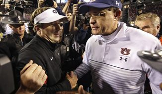 Auburn head coach Gus Malzahn, right, congratulates Georgia head coach Kirby Smart after an NCAA college football game, Saturday, Nov. 16, 2019, in Auburn, Ala. Georgia won 21-14. (Bob Andres/Atlanta Journal-Constitution via AP)