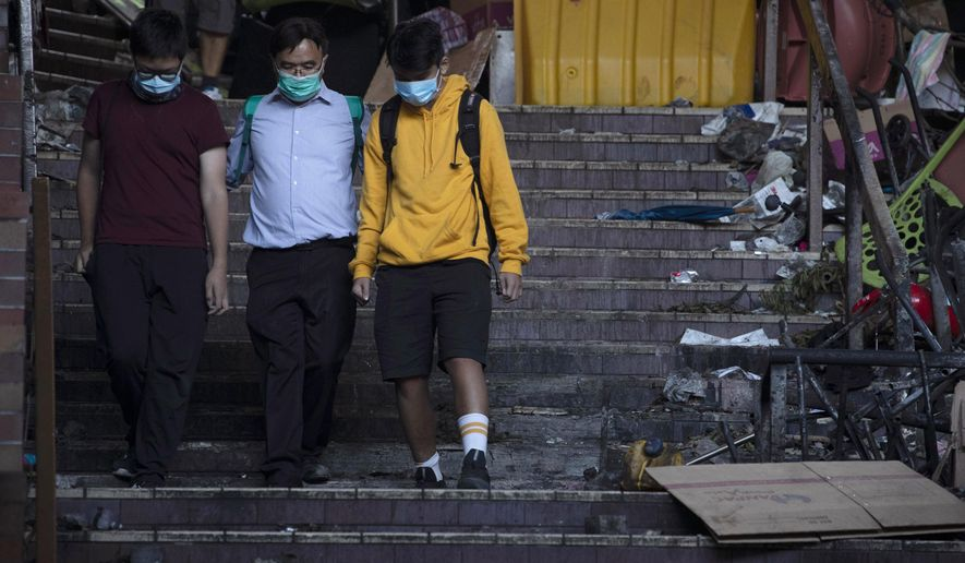 A school principal, center, escorts two youths to surrender to the police at the Hong Kong Polytechnic University in Hong Kong on Tuesday, Nov. 19, 2019. Police tightened their siege of the university campus where hundreds of protesters remained trapped overnight Tuesday in the latest dramatic episode in months of protests against growing Chinese control over the semi-autonomous city. (AP Photo/Ng Han Guan)