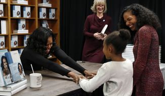 """Former first lady Michelle Obama holds hands with Kaitlyn Saunders, 8, next to her mother Katrice Saunders, of Washington, after the 8-year-old told Obama how inspired she is by her and how she is a competitive figure skater, as they buy signed copies of Obama's book, """"Becoming,"""" Monday Nov. 18, 2019, at Politics and Prose Bookstore in Washington. (AP Photo/Jacquelyn Martin)"""