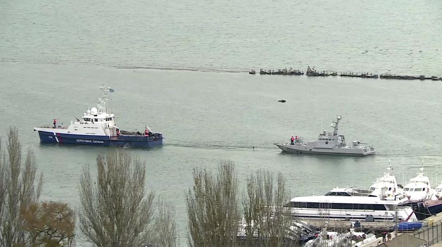 This video grab provided by the Krym 24 tv station via AP Television shows a seized Ukrainian ship, right, being towed by a Russian coast guard boat out of the port in Kerch, Crimea, Sunday, Nov. 17, 2019. Russia's Foreign Ministry says three Ukrainian naval ships that were seized in a shooting confrontation nearly a year ago have been returned. (Krym 24 tv station via AP Television)