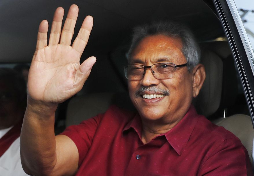 Sri Lanka's President-elect Gotabaya Rajapaksa waves to supporters as he leaves the election commission after the announcement of his victory in Colombo, Sri Lanka, Sunday, Nov.17, 2019. Rajapaksa, revered by Sri Lanka's ethnic majority for his role in ending a bloody civil war but feared by minorities for his brutal approach, declared victory Sunday in the nation's presidential election. (AP Photo/Eranga Jayawardena)