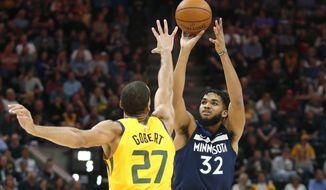 Minnesota Timberwolves center Karl-Anthony Towns (32) shoots as Utah Jazz center Rudy Gobert (27) defends in the first half during an NBA basketball game Monday, Nov. 18, 2019, in Salt Lake City. (AP Photo/Rick Bowmer)