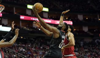 Houston Rockets' James Harden (13) goes up for a shot as Portland Trail Blazers' Skal Labissiere, right, defends during the first half of an NBA basketball game Monday, Nov. 18, 2019, in Houston. (AP Photo/David J. Phillip)