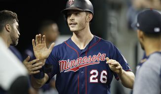 FILE - In this Aug. 30, 2019, file photo, Minnesota Twins' Max Kepler is greeted in the dugout after scoring during the eighth inning of the team's baseball game against the Detroit Tigers,  in Detroit. Kepler is in Germany for a five-day Major League Baseball promotional tour. He reminisced about Little League ball in the German capital. He said his dad gave tips on preparation and recovery, his mom on motivation. (AP Photo/Carlos Osorio, File)