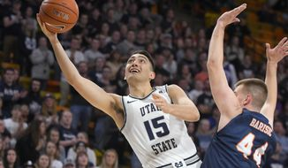 Utah State guard Abel Porter (15) takes a shot as UTSA forward Luka Barisic (44) defends during the first half of an NCAA college basketball game Monday, Nov. 18, 2019, in Logan, Utah. (AP Photo/Eli Lucero)