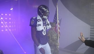 Baltimore Ravens quarterback Lamar Jackson (8) walks with a U.S. service member before being introduced on the field as part of the team's Salute to Service prior to an NFL football game against the Houston Texans, Sunday, Nov. 17, 2019, in Baltimore. (AP Photo/Nick Wass)  **FILE**