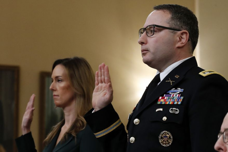 Jennifer Williams, an aide to Vice President Mike Pence, and National Security Council aide Lt. Col. Alexander Vindman, are sworn in before they testify before the House Intelligence Committee on Capitol Hill in Washington, Tuesday, Nov. 19, 2019, during a public impeachment hearing of President Donald Trump's efforts to tie U.S. aid for Ukraine to investigations of his political opponents. Attorney Michael Volkov is seated right. (AP Photo/Alex Brandon)