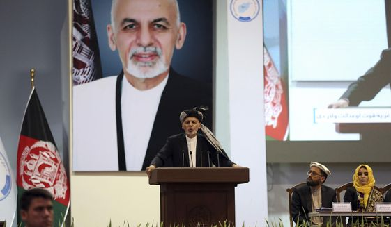 FILE - In this May 3, 2019, photo, Afghan President Ashraf Ghani speaks on the last day of the Afghan Loya Jirga meeting in Kabul, Afghanistan. Taliban officials have told The Associated Press that three Taliban prisoners released by Kabul have been flown to Qatar for a swap for an American and an Australian hostage held by the insurgents. The three Taliban prisoners were to have been freed more than one week ago by Afghan President Ashraf Ghani. (AP Photo/Rahmat Gul, File)