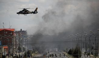 An Army helicopter flies over the road leading to the state-own Senkata filling gas plant in El Alto, on the outskirts of La Paz, Bolivia, as supporters of former President Evo Morales set up barricades, Tuesday, Nov. 19, 2019. Morales' backers have taken to the streets asking for his return since he resigned on Nov. 10 under pressure from the military after weeks of protests against him over a disputed election he claim to have won. (AP Photo/Natacha Pisarenko)
